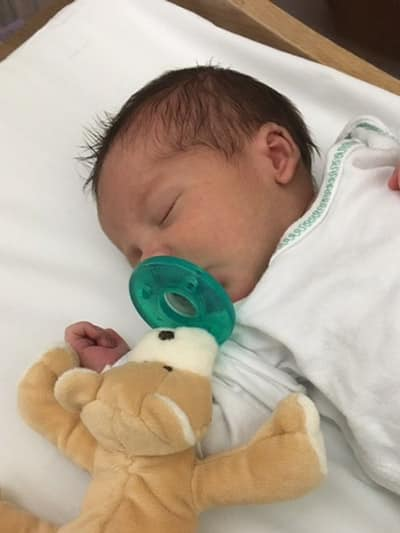 Premature baby sucking on a WubbaNub pacifier